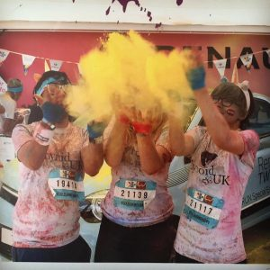 three women throwing yellow powder after completing a 5k color run
