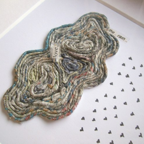 "newspaper yarn design of colorful cloud with raindrops and text saying ""love the rain"""