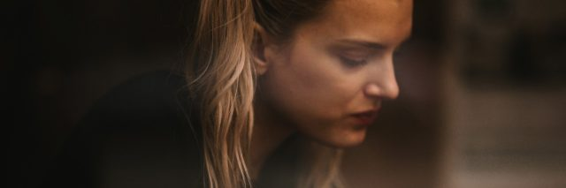 Side profile photo of young blonde woman looking depressed