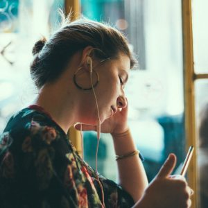 young woman in public space listening to music on earphones