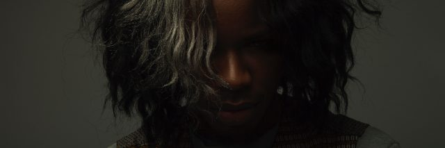 woman of color against dark background looking down from camera