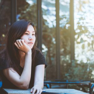 Asia youth teenager sitting depression on chair. Lifestyle people concept in cafe.
