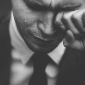 black and white image of man wearing suit crying with tear on cheek