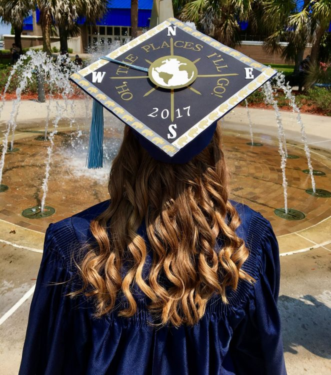 college graduate standing in front of a fountain wearing her cap and gown