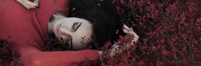 young woman lying in bush with small red leaves wearing red sweater