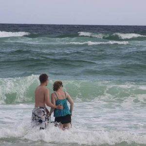 The author standing in the ocean with her walker, with her son standing next to her