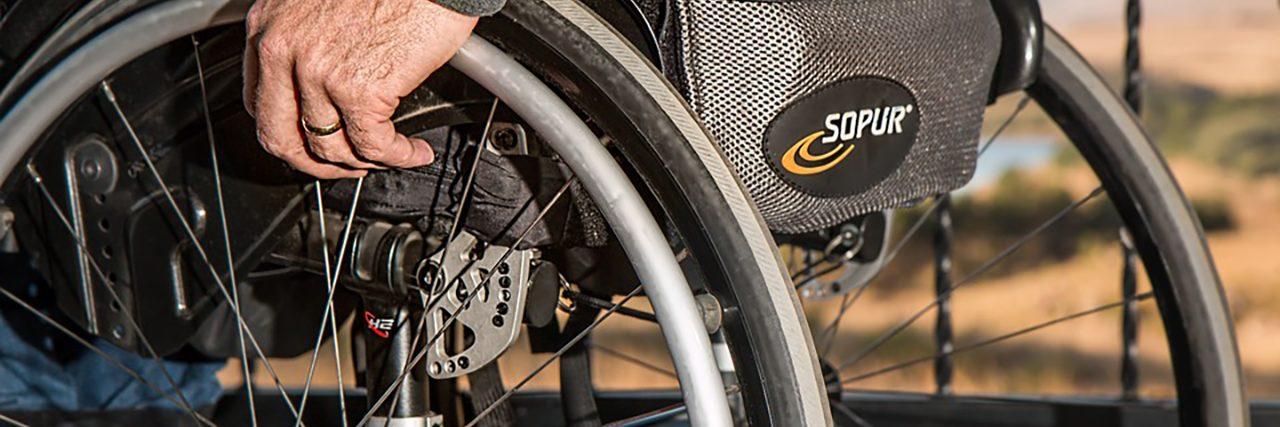 Man pushing his manual wheelchair.
