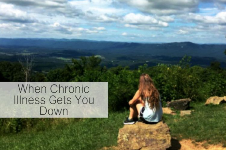 young woman sitting on a rock overlooking a valley with text saying 'when chronic illness gets you down'