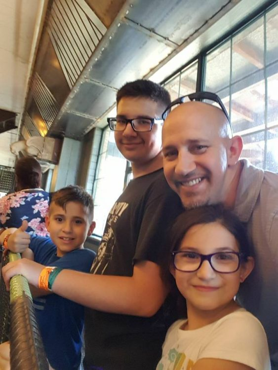 dad smiling with three kids