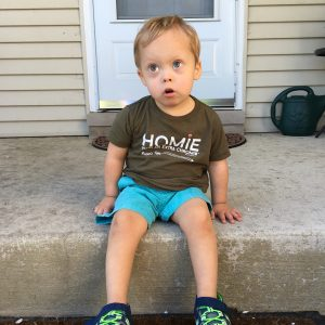 Little boy with Down syndrome sitting on a step