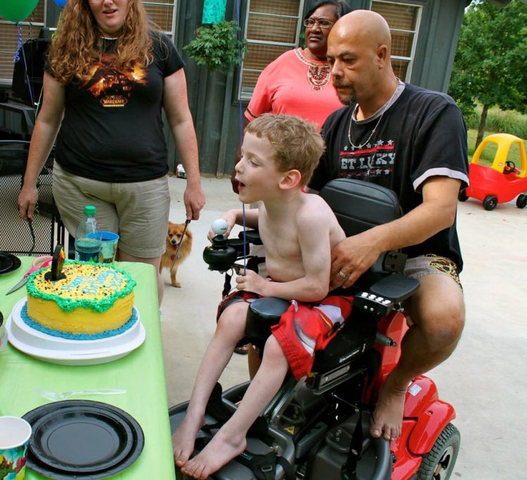 dad helping son in wheelchair blow out candles on his birthday cake