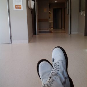 image of woman's shoes as she sits down in a hallway