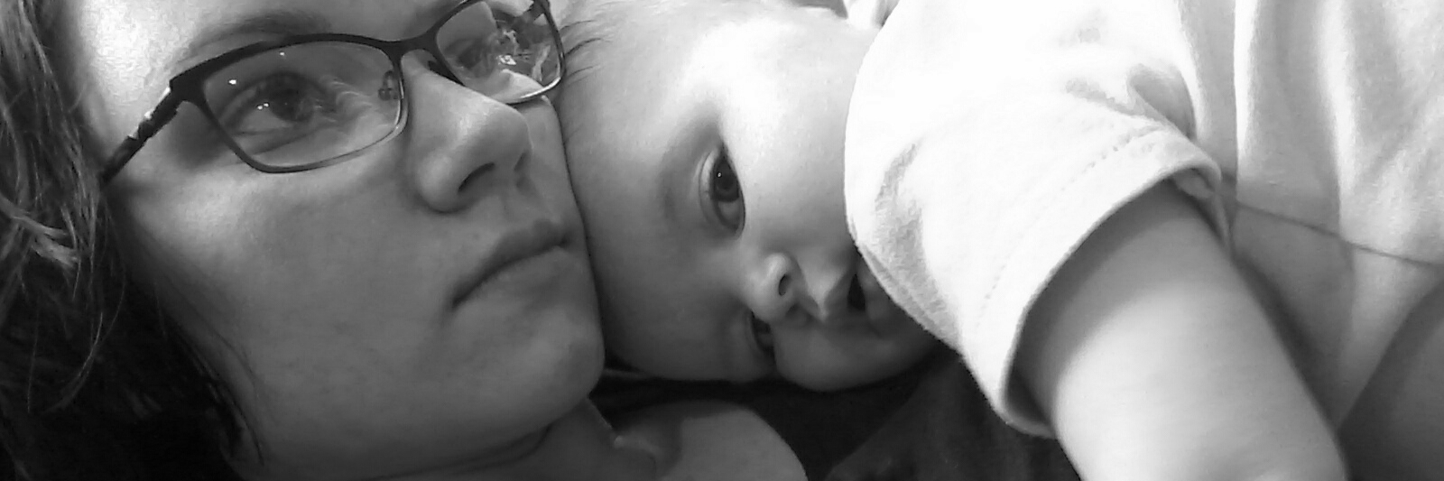 black and white photo of woman lying down with baby sleeping on top of her