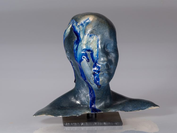 ceramic head with blue paint running down the side