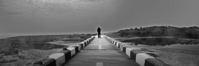 black and white photo of a person walking down a long road