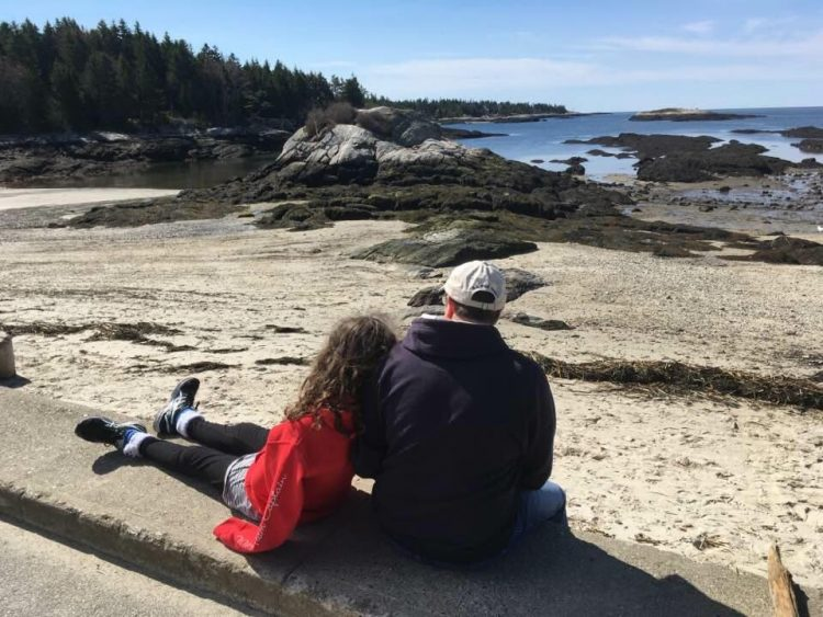 dad supporting daughter next to the beach