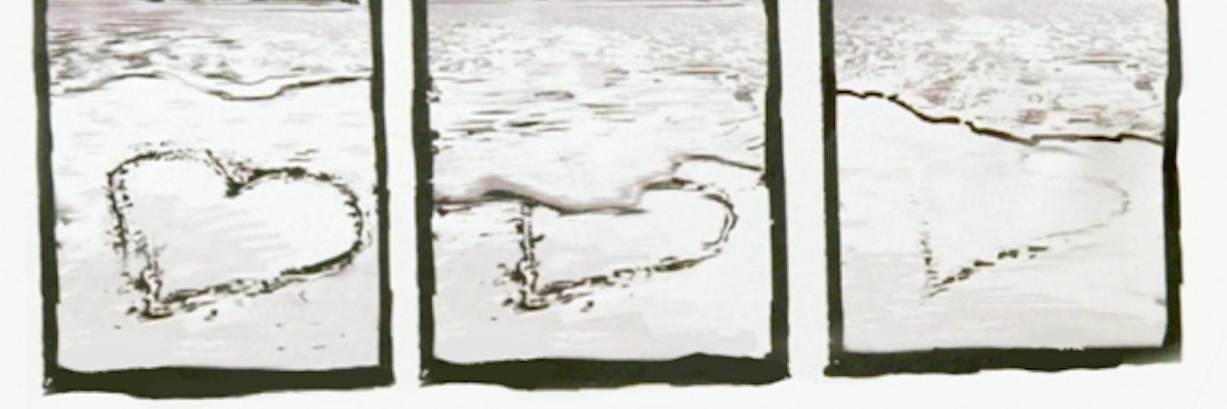 heart drawn in sand getting slowly erased by the ocean