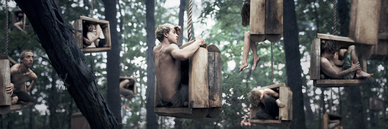 an abstract image of men sitting in boxes hanging from trees