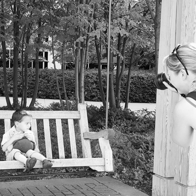 Black and white photo of photographer taking picture of a child with autism sitting on a swing bench