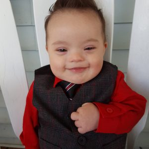 Little baby boy with Down syndrome smiling, his thicj dark hair is styled sticking up like a Mohawk and he is wearing a suit with a red shirt