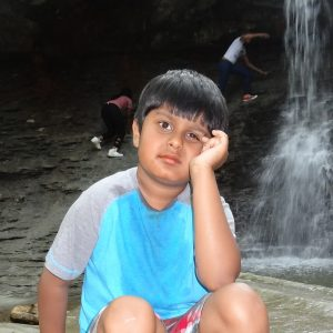 The author's son, sitting on a rock next to a waterfall