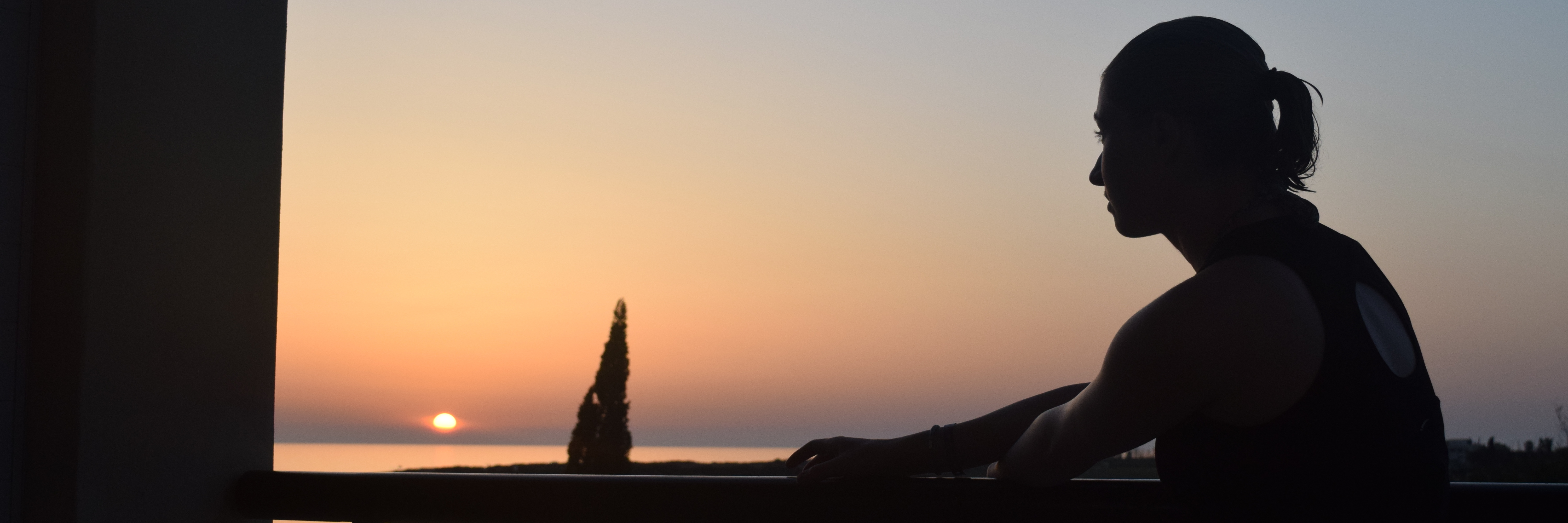 silhouette of a woman standing on a balcony overlooking a lake at sunset