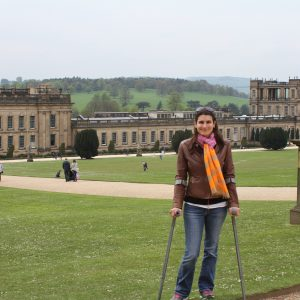 woman using walking devices and standing in front of large building