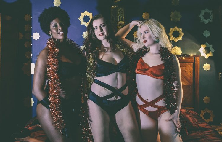 Three women with ostomies wearing lingerie