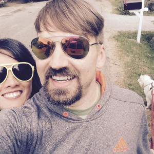 woman and man selfie smiling wearing sunglasses with dog in background