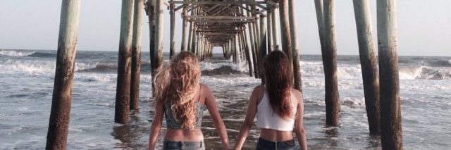 two sisters holding hands under a pier at the beach