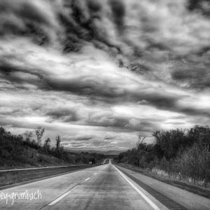 A black and white picture of an empty road on a cloudy day.