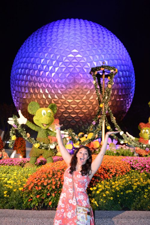 woman smiling and waving her arms in front of epcot at disney
