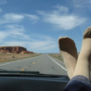 woman's feet propped up on the dashboard of a car on a road trip