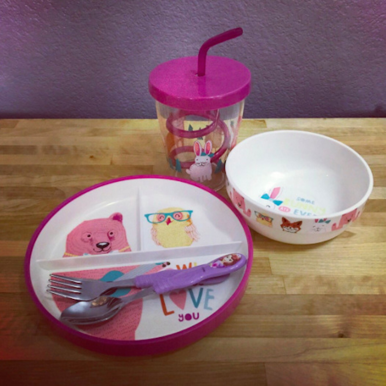 Child's plate with illustrations of animals on it, plus matching bowl, cup with a straw and eating utensils