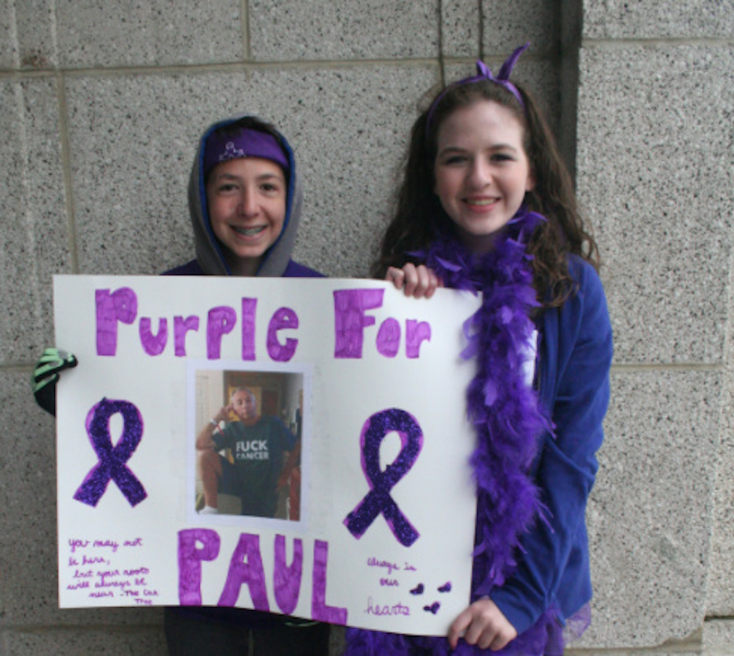 """Two people holding a handmade sign that says """"Purple for Paul"""" with a photo and purple ribbons"""