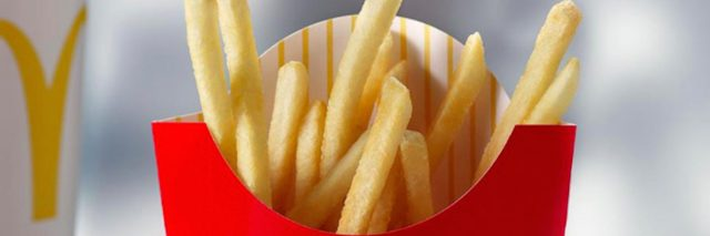 McDonald's french fries on a table next to a McDonald's beverage cup