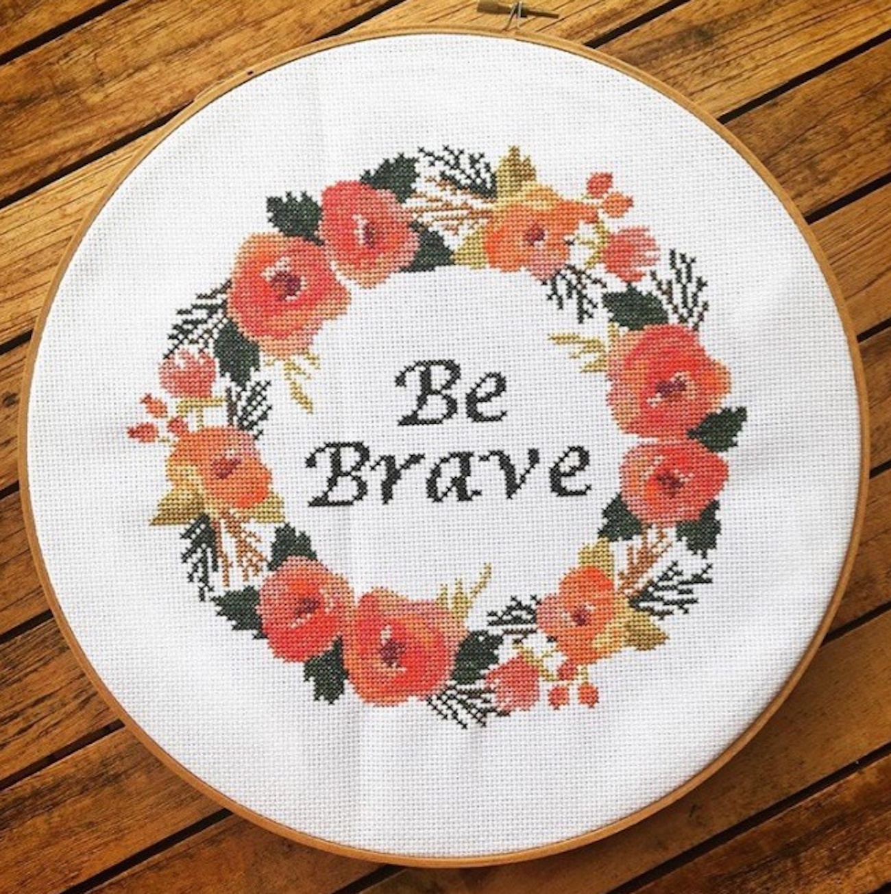 Cross-stitched framed image of the words be brave surrounded by a ring of flowers
