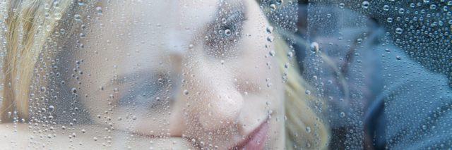 depressed woman resting head on arm near rainy window
