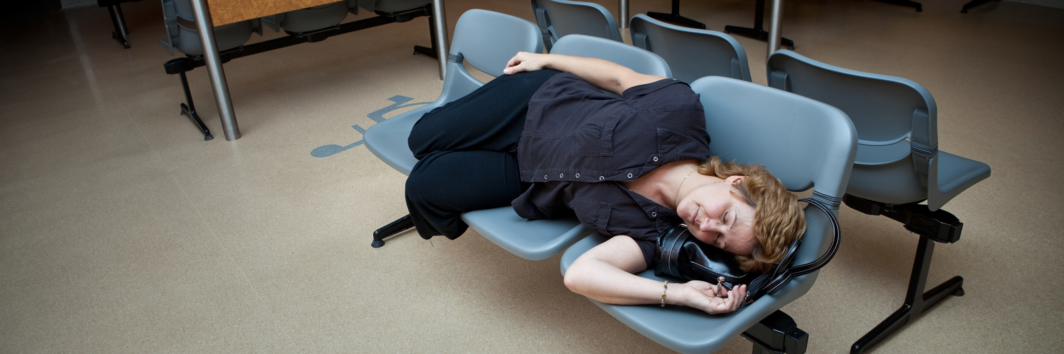 Woman laying on waiting room seats in the hospital.