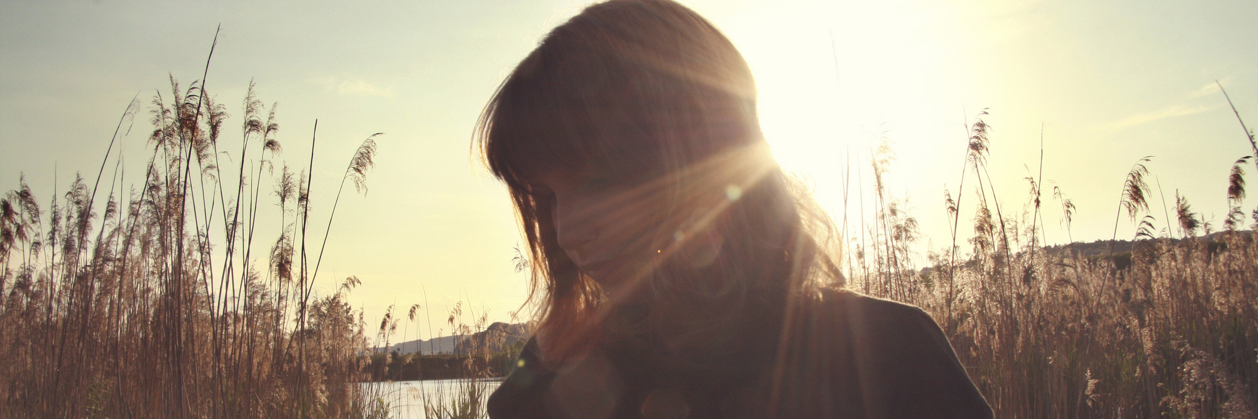 woman mostly silhouetted by sunlight in field with muted colours