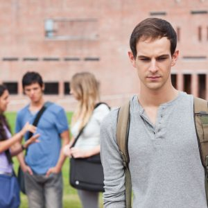 lonely male student standing with group of students gossiping behind him