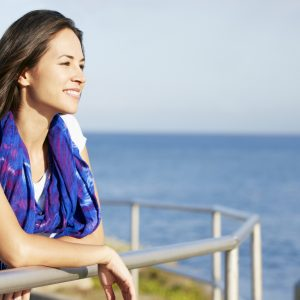 woman smiling and leaning on a rail overlooking the ocean