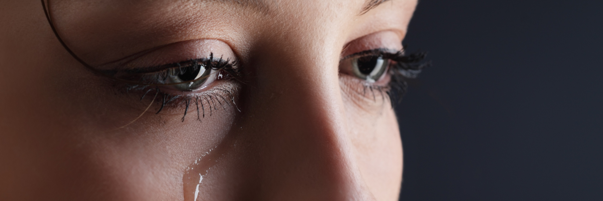 young woman with dark background with tear on cheek