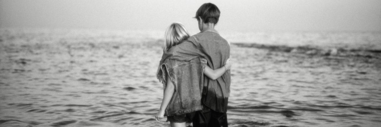 Girl (6-7) and boy (8-11) walking in sea, rear view