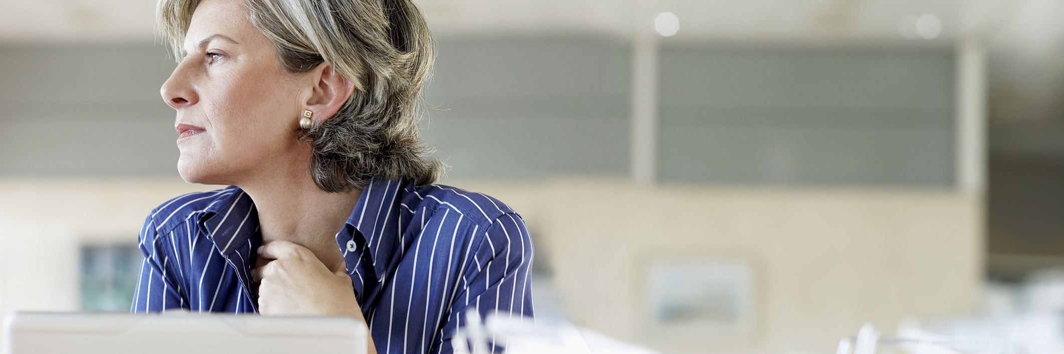 woman sitting at her desk looking away from her computer