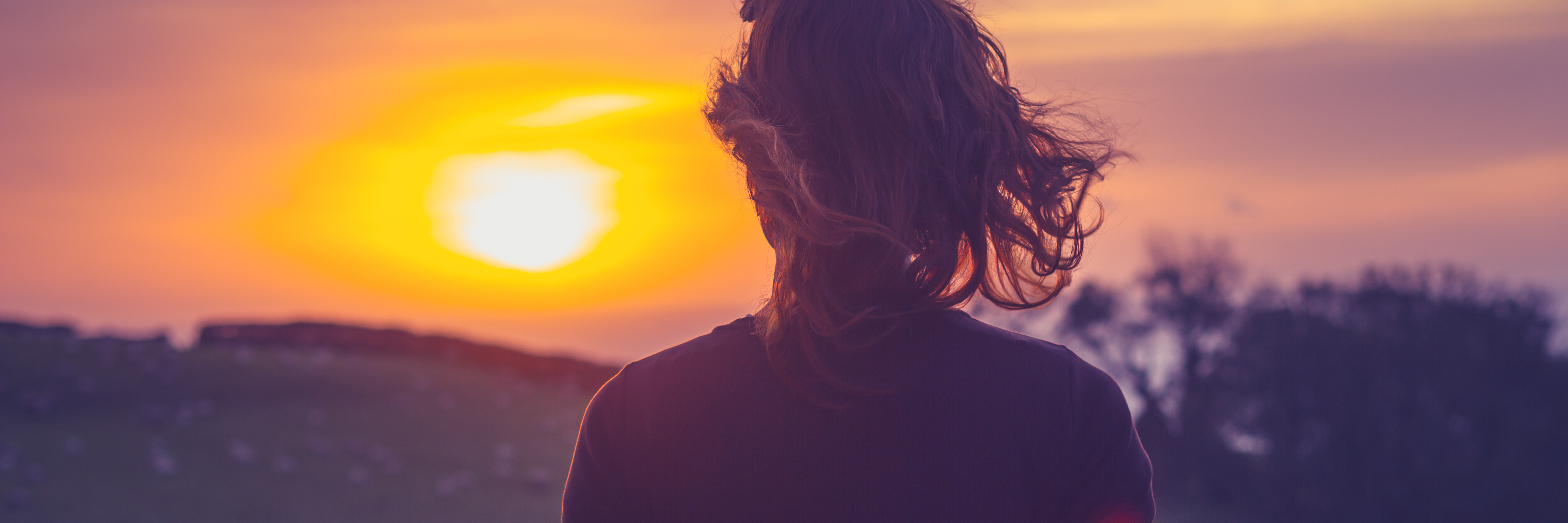 young woman watching sunset from balcony