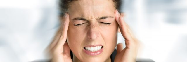woman feeling dizzy and holding her head