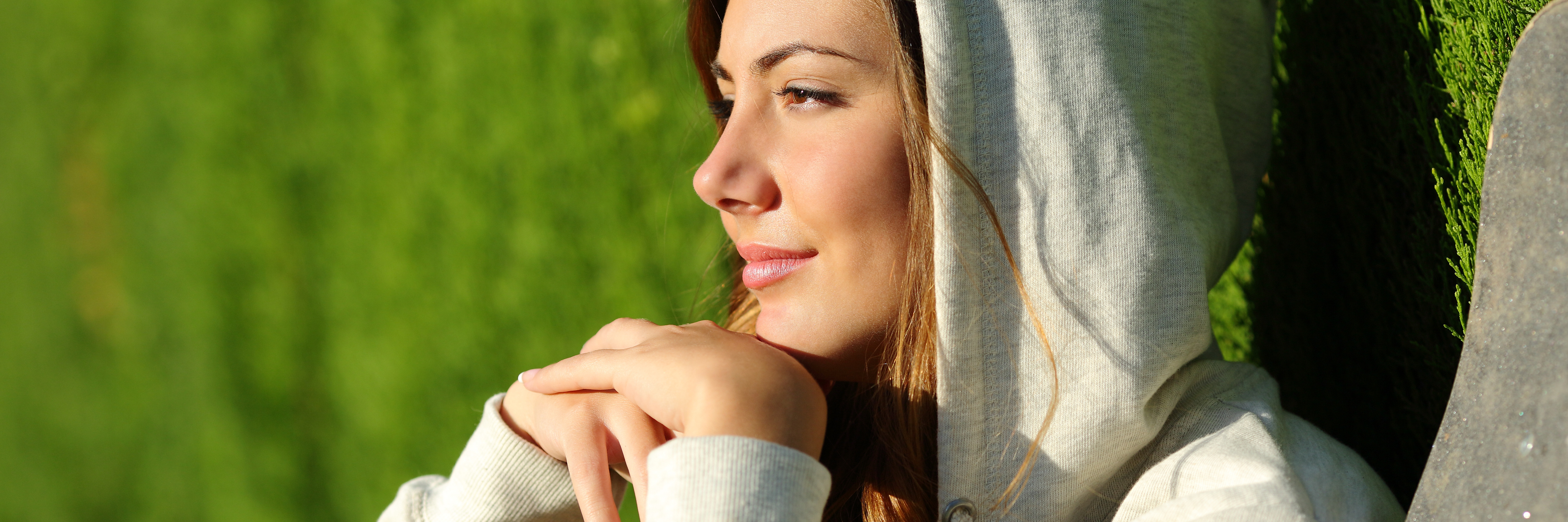 young woman staring out over sunset looking pensive
