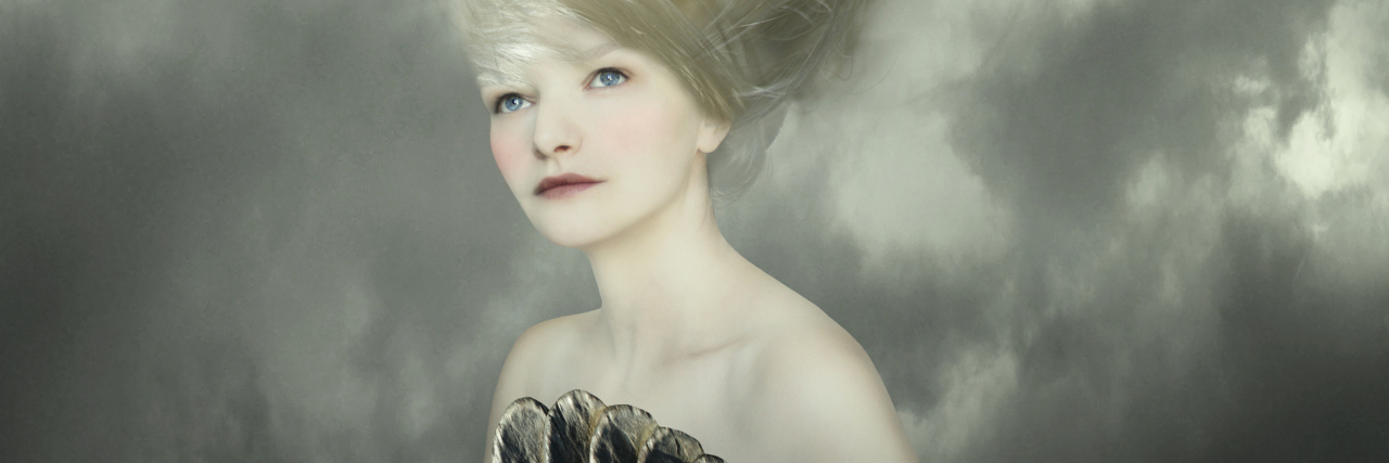 Sophisticated and artistic portrait of a beautiful female model with a white dove on a branch in the very long blond hair