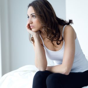 woman sitting on her bed and looking upset